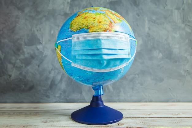 Globus in einer medizinischen schutzmaske. coronavirus greift den planeten an.