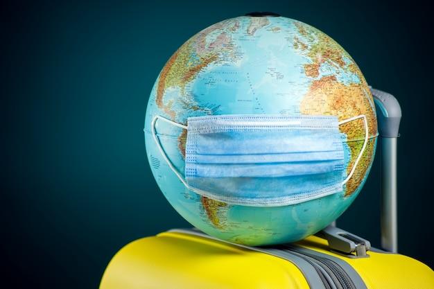 Globus mit medizinischer gesichtsmaske auf gepäck. reise- und coronavirus-konzept.
