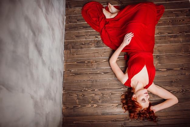 Glorious frau im roten kleid liegt auf dem holzboden