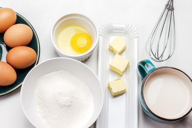 Glour in einer schüssel, milch in einer tasse, butter auf dem teller und braune eier in grauer schüssel auf weißem hintergrund