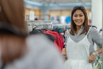 Glückliche asiatische Frau, die Kleidung mit Reflexion des Glases wählt