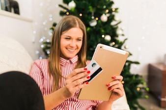 Glückliche Dame, die Tablette und Kreditkarte nahe Weihnachtsbaum hält