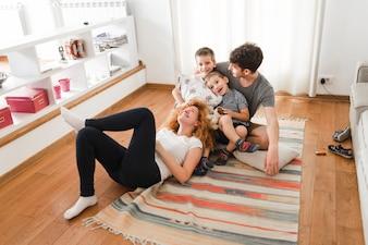 Glückliche Familie, die heraus im Wohnzimmer hängt