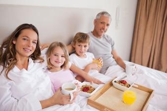 Glückliche Familie, die in einem Schlafzimmer frühstückt