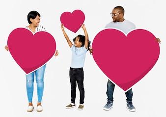 Glückliche Familie, die rote Herzikonen hält