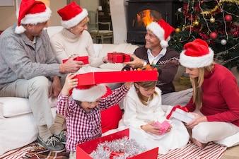 Glückliche Familienöffnungs-Weihnachtsgeschenke zusammen zu Hause im Wohnzimmer