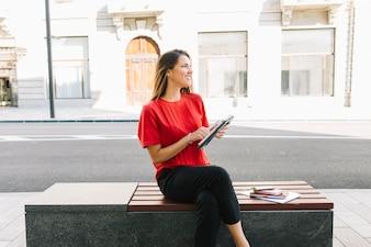 Glückliche Frau, die auf Bank mit Tagebuch sitzt