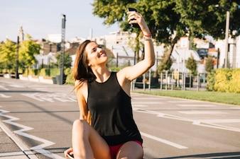 Glückliche Frau, die auf dem Skateboard nimmt Selfie mit Mobiltelefon sitzt