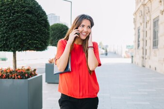Glückliche Frau, die auf Smartphone in der Stadt spricht