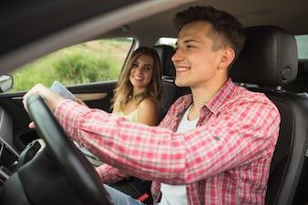 Glückliche Frau, die den Mann fährt Auto betrachtet