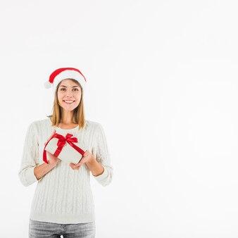 Glückliche Frau, die mit kleiner Geschenkbox steht