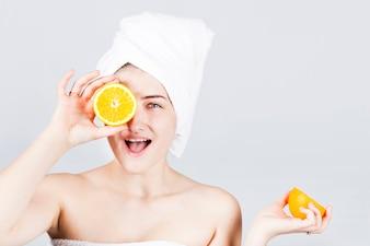 Glückliche Frau im Tuch mit Orangen am Gesicht