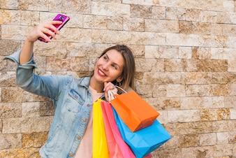Glückliche Frau mit den Einkaufstaschen, die selfie nehmen