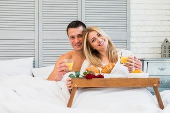 Glückliche Frau und Mann mit Gläsern im Bett nahe Lebensmittel auf Frühstückstische