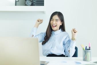 Glückliche junge asiatische Geschäftsfrau beendete ihre Arbeit am Arbeitsplatz.