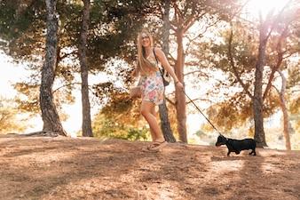Glückliche junge Frau, die das Buch geht mit ihrem Hund im Garten hält