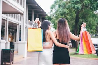 Glückliche junge Frauen mit den Einkaufstaschen, die im Einkauf am Feiertag genießen.