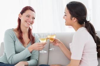 Glückliche junge Freundinnen, die zu Hause Weingläser rösten