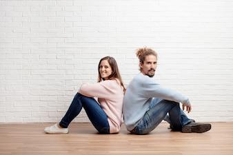 Glückliche junge Paare, die auf dem Boden ihres neuen Hauses sitzen. Konz
