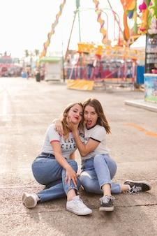 Glückliche Mädchen, die Spaß im Vergnügungspark haben