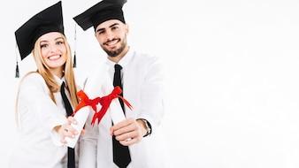Glückliche Menschen, die mit Diplomen stehen
