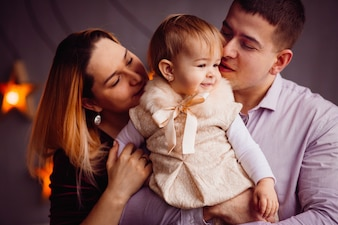 Glückliche Mutter und Vati halten charmante kleine Mädchen in ihren Armen