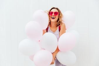 Glückliche schöne junge Frau in der rosa Sonnenbrille hält weiße Ballone und lächelt nett
