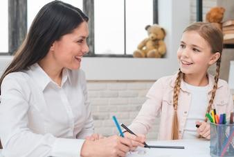 Glückliche weibliche Psychologe- und Mädchenzeichnung mit farbigem Bleistift und Filzstiften auf Papier