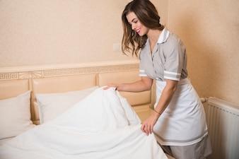 Glückliche Zimmermädchen, die das Bettlaken im Hotelzimmer ändert