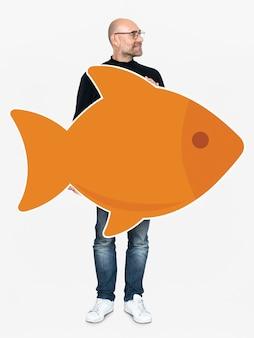 Glücklicher Mann, der einen orange Fisch hält