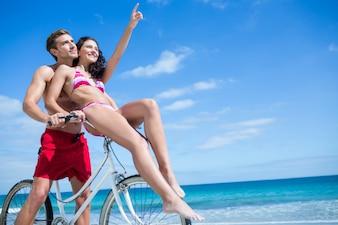 Glückliches Paar, das auf eine Fahrradfahrt am Strand geht