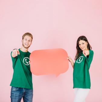 Glückliches Paar, das Finger beim Halten der leeren orange Spracheblase zeigt