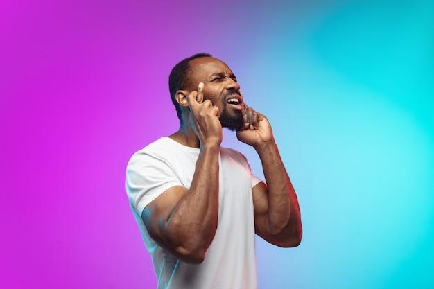 Glück, daumen drücken. porträt des afroamerikanischen jungen mannes auf studiohintergrund in neon. schönes männliches model im lässigen stil, weißes hemd. konzept der menschlichen emotionen, gesichtsausdruck, verkauf, anzeige.