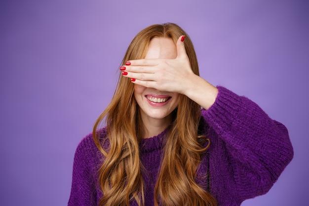 Glück, emotionen und vorfreude-konzept. charmante verträumte ingwer-freundin mit süßen nägeln, die die augen mit erhobener handfläche bedecken und breit lächeln, die auf überraschung oder wunder warten und peekaboo spielen.