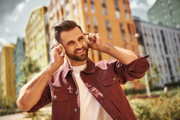 Glück. fröhlicher junger mann mit stoppeln in kopfhörern, der musik hört und lächelt, während er auf der straße steht. inspiration. musikkonzept. klang