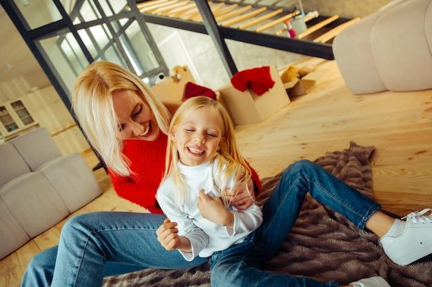 Glück fühlen. begeisterte frau, die positivität ausdrückt, während sie ihr kind umarmt