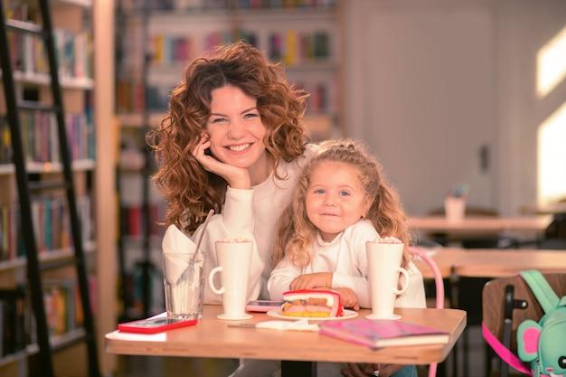 Glück fühlen. freundliches kleines mädchen, das arme auf tisch lehnt, während sie lieblingscafé mit ihrer mutter besucht