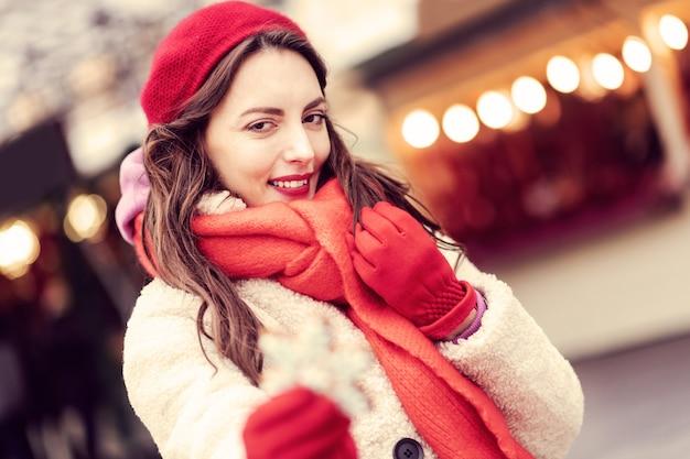 Glück fühlen. nette brünette frau, die ihr haar berührt, während fotograf betrachtet
