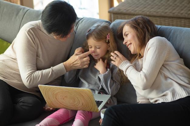 Glück. glückliche liebevolle familie. großmutter, mutter und tochter verbringen zeit miteinander. kino schauen, laptop benutzen, lachen. muttertag, feier, wochenende, urlaub und kindheitskonzept.