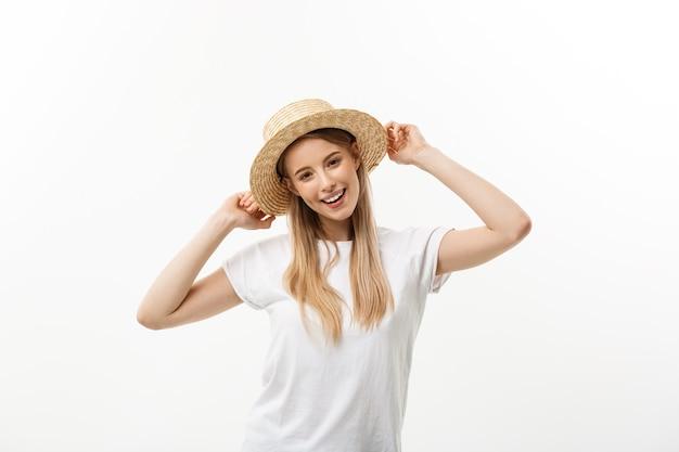 Glück. glückliche sommerfrau lokalisiert im studio. energetisches frisches porträt der jungen frau aufgeregt beim tragen von strandhut zujubeln.