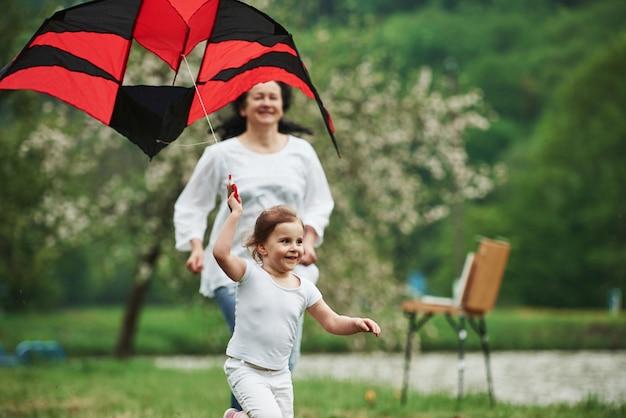 Glück ist in einfachen dingen. positives weibliches kind und großmutter, die mit rotem und schwarzem drachen in den händen draußen laufen
