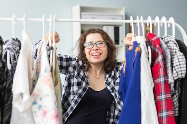 Glück, kleidung, menschenkonzept - eine glückliche frau, die ihre garderobe genießt