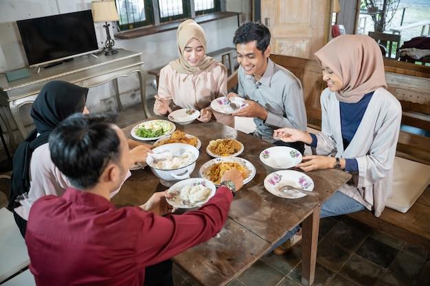 Glück mit freunden, die sich beim essen beim ramadan-fest versammeln