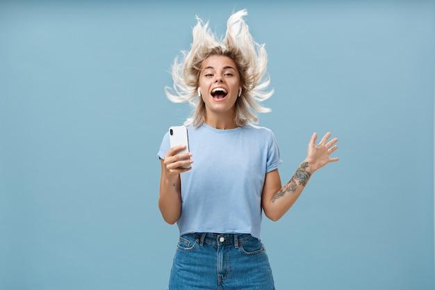 Glück mit hilfe großartiger melodien ausdrücken. freudige amüsierte und glückliche gutaussehende junge studentin, die spaß beim hören von musik in drahtlosen ohrhörern springt und das smartphone über der blauen wand hält