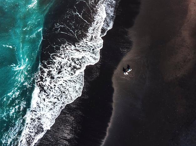 Glück-paare, die auf schwarzem sandstrand mit weißer welle bei bali, indonesien genießen