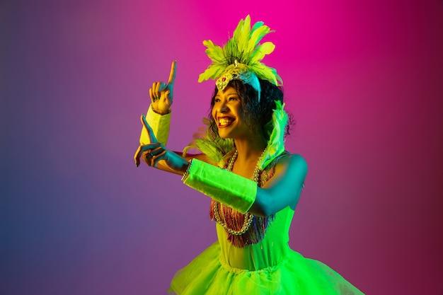 Glück. schöne junge frau im karneval, stilvolles maskeradekostüm mit federn, die auf steigungshintergrund in neon tanzen. konzept der feiertagsfeier, festliche zeit, tanz, party, spaß haben.