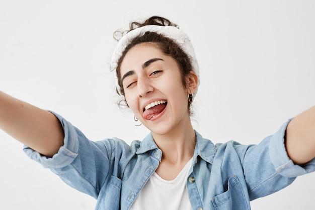Glück, schönheit, freude und jugend. junges positives mädchen gekleidet in jeanshemd über weißem t-shirt, das arme streckt, breit lächelt, blinzelt, ihre zunge herausstreckt, gute laune hat.