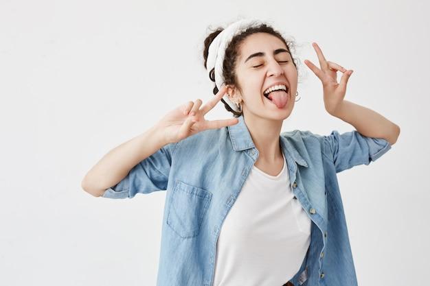 Glück, schönheit, freude und jugend. junges positives mädchen gekleidet in jeanshemd über weißem t-shirt, das v-zeichen zeigt, breit lächelnd, mit geschlossenen augen, ihre zunge herausstreckend, gute laune habend.