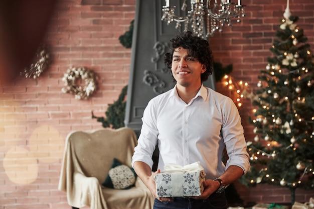 Glück steckt in kleinen dingen. junger mann, der im schönen dekorierten raum steht und weiße geschenkbox im neuen jahr hält.