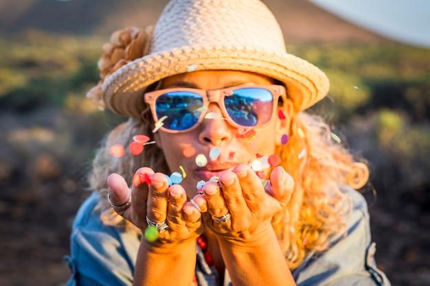 Glück und feiern im freien mit fröhlicher freude erwachsene junge frau, die buntes konfetti aus den händen bläst - partykonzept-porträtbild mit hübscher frau, die spaß hat